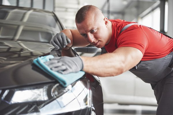 car detailer rubbing vehicle with rag