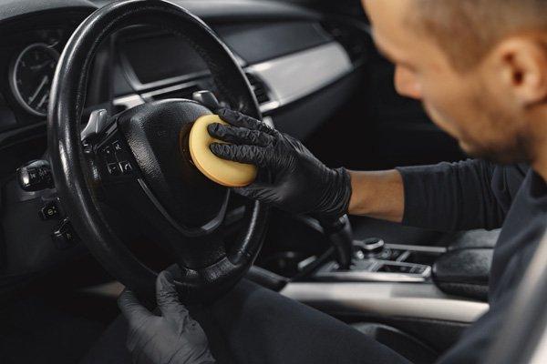 man using sponge to clean car badge