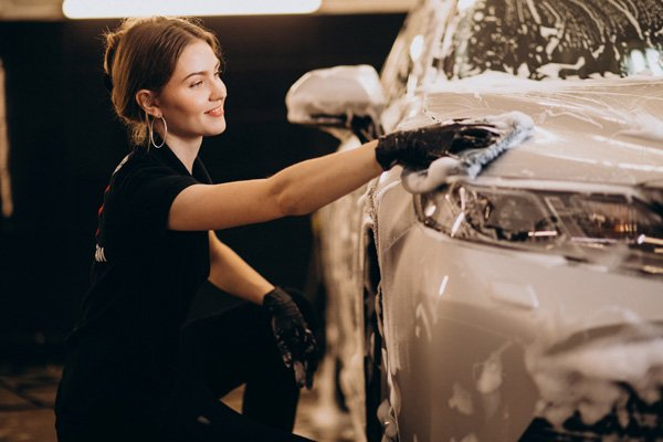 car cleaning woman detailing vehicle exterior